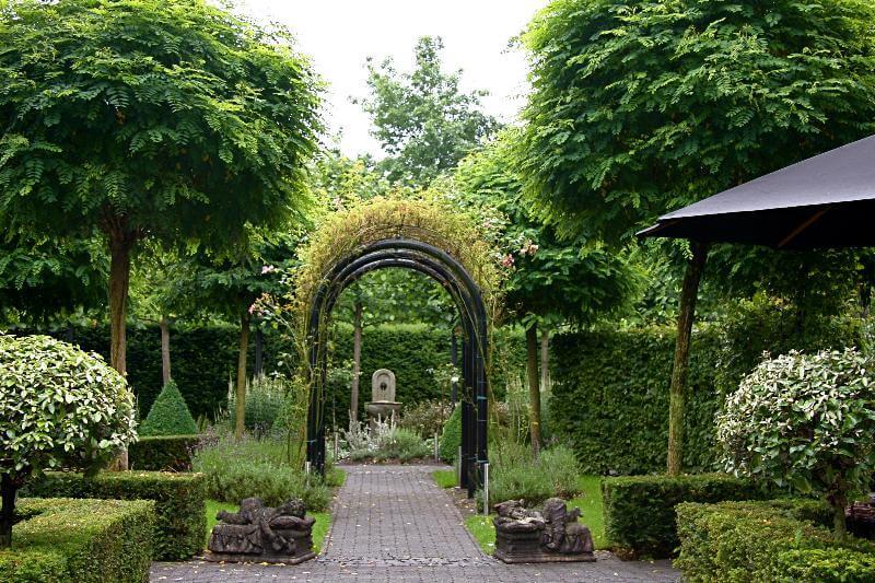 Romantische tuin met rozenbogen